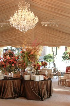 Stick with a single, dramatic chandelier to really make a statement in your wedding tent. In this case, the chandelier hangs in the center of the tent over a beautifully arranged appetizer bar.