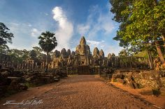Angkor Thom Siem Reap Province-Cambodia - Prasat Bayon -  Arriving on a motorbike, the shape of the temple appear through trees and vegetation, the sun has just risen and the light is still golden. It is still early, the temple is almost deserted, the towers with smiling faces invested by the rays of the sun, set against a blue sky. The temple sits at the exact center of Angkor Thom. by Emanuele Del Bufalo