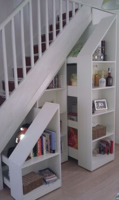 Pull out stair bookcases in white. http://www.arthanfurniture.co.uk/wooden
