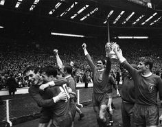 Liverpool skipper Ron Yeats (centre) holds the FA Cup aloft and raises his arms in triumph as his victorious team do a lap of honour following the Reds first triumph in the competition in 1965