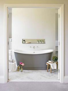 Elégante et épurée, la baignoire de couleur grise prend une place centrale