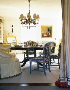 At the round English Regency-style table, dining chairs are paired with a curved banquette upholstered in Cowtan & Tout's Lucerne in yellow. The 1960s French chandelier is from Amy Perlin.   - HouseBeautiful.com