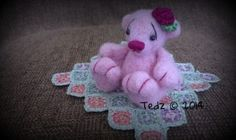 Needle felted miniature teddy bear, with contrasting embroidered face and paws, and a matching crocheted rose.  She also has hand made polymer clay eyes.