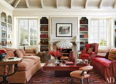 In the library of Hilary and Galen Weston's Florida home, designer John Stefanidis conceived the stone fireplace, detailed with a large central scallop shell and conch-shell finials to either side; the throw pillows are of Indian silks. Coastal Living Rooms, Fireplace Design, Florida Home, Architectural Digest, Home Decor Inspiration, Decor Ideas, Room Ideas, Interiores Design, Decoration
