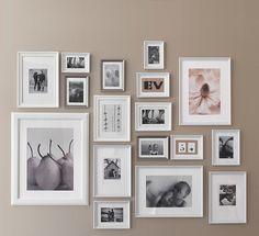 Væg dekoreret med hvide og sølvfarvede rammer i forskellige størrelser. Vist med familiebilleder og plakater.