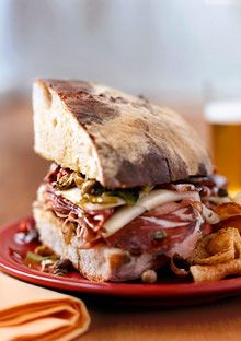Muffuletta Sandwich Recipe The muffuletta, a classic invented by Italian expats in New Orleans, is jam-packed with spicy cured meat, garlicky olive salad and piles of provolone and Swiss. Best Sandwich, Soup And Sandwich, Sandwich Recipes, Muffuletta Sandwich, Burgers And More, Cookout Food, Delicious Burgers, Wrap Sandwiches, Side Recipes