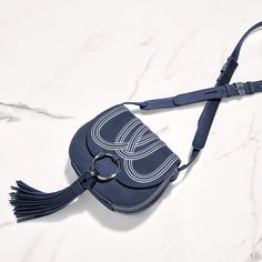Seventies, equestrian-inspired chic: The Tassel Mini Saddlebag is a standout style from our runway. The easy shape is made of leather that's printed with swirling stripes and embossed by hand. Featuri