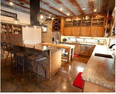 Modern rustic kitchen with concrete counter-tops, stained concrete floor, and a ceiling of rusting corrugated metal. Concrete Kitchen, Concrete Countertops, Concrete Floors, Kitchen Flooring, Corrugated Tin Ceiling, Metal Ceiling, Corrugated Metal, Roof Ceiling, Ceiling Fans