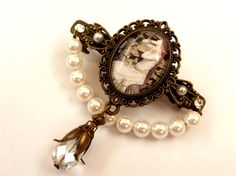 This small barrette in antique style is a beautiful accessory for an updo. It consists of bronze hair clip with metal hair clips mechanics (width 4.8 cm). On the front there is a jewelry holder with handmade glass cabochon, which shows a beautiful vintage scene with girl on a tree. The side parts of the hair clip decorated with half pearls and rhinestones brand in crystal clear. Down at the eye of the jewelry holder is a pendant with a faceted cut glass pearl. The special highlight is the…
