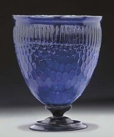 A ROMAN GLASS GOBLET  CIRCA 4TH CENTURY A.D.  Translucent dark blue in color, the deep ovoid beaker mold-blown and further inflated, with vertical fluting below the rim, elaborate honeycomb pattern on the body, the honeycombs distended toward the base, the rim flaring slightly and cut off, the profiled foot with a beaded stem  8 in. (20.3 cm.) high