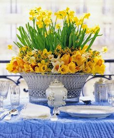 Carolyne Roehm of course….I love the French steel wicker basket this is in…also the wreath of lower flowers surrounding the daffodils!