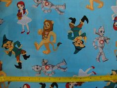 Wizard of Oz Dorothy Scarecrow Tin Man Lion Cartoon Character Toss on Blue Cotton Fabric by NY Collections