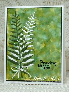 By Bonnie Klass. Alcohol ink background. Stamp sentiment. Die cut fern 3 times, once from white, once from green, and once from the background. Layer background onto black mat then white card base. Fit white fern into the negative space in the background. [This is called embedding or inlaying.] Attach green fern and twine bow.