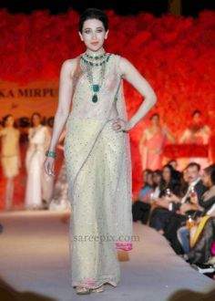 Bollywood ageless beauty Karishma kapoor ramp walk in transparent sari. Karishma kapoor is looking awesome in transparent netted designer saree with sleeveless and backless blouse.