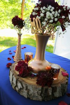 Sweetheart table. Centerpiece. Rose gold Navy White Burgundy. Walnut wood round. Rose gold mercury candles. Burgundy berry dahlias. Black baccara roses. Baby's breath.