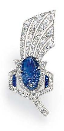 A SAPPHIRE AND DIAMOND BROOCH Designed as a single and circular-cut diamond stylized feather, centering upon an oval carved sapphire, with calibré-cut sapphire detail, mounted in platinum, with French assay mark