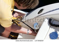 Sold at Shutterstock: Man connecting power cord to inlet of boat. by eZeePics Studio, via ShutterStock