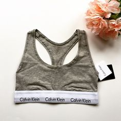 """CK Gray Bralette Gray Calvin Klein bralette/sports bra. Have the thicker 1"""" logo band. Part of the modern cotton collection, super soft and comfy. Celeb favorite! Bundle with other CK bralettes and panties in my closet for a discount. Reasonable offers can be made through offer button   Condition: Brand new, never worn.  Trades  Please ask any questions prior to purchasing. All sales final. Calvin Klein Intimates & Sleepwear Bras"""