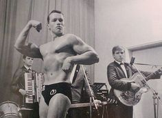 Check out a young Arnold Schwarzenegger showing off his muscles at his first bodybuilding contest in Austria! It looks like the guitar player is a bit jealous of Arnold's physique.