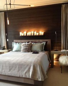 '39 Jaw-dropping wood clad bedroom feature wall ideas' - love the candles above the headboard.