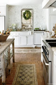 INTERIOR DESIGN BY LISA LUBY RYAN   - Veranda.com | wonderful Christmas decorations | decorating the kitchen | interesting idea with a mirror over the sink. Love that there are no upper cabinets. #whitekitchen