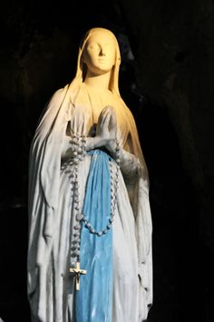 Statue of Our Lady of Lourdes, in the grotto of apparitions: How to place a petition and candle at Lourdes.