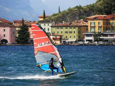 Windsurfers ride Lake Garda, one of Italy's most popular vacation spots, featuring resort towns, hot springs and terra-cotta-roofed hotels.