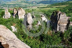 Megaliths in the geological park of Gradina Zmeilor in Romania. Tall stone structures rise from between the trees. In the distance there is a traditional village. Geology, Romania, Distance, Travel Destinations, Scenery, Trees, Europe, Stock Photos, Traditional