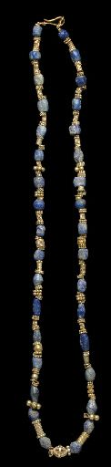 A WESTERN ASIATIC GOLD AND LAPIS LAZULI BEAD NECKLACE   CIRCA EARLY 1ST MILLENNIUM B.C.   Composed of thirty-four lapis lazuli beads of various forms, interspersed with gold beads, primarily disks formed of granulation of various sizes, centered by an openwork biconical bead; strung with a modern hook-and-loop closure  21 7/8 in. (55.6 cm.) long