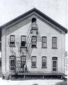 Rudolph Roschman standing in front of button factory, 1900. Waterloo, Ontario.