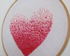 The assignment in a classroom inspired me of this hand embroidered hoop. A girl used her pencil rubber and ink painted a heart in different red dots, from dark to light shades.  I love to create my arts in heart shape, so I started stitching this item in my shop. It was so simple but one of a kind and looks stunning on a house wall.  This hoop measure 6 inch. The back is left uncovered and ready to hang.   For International buyers, please convo me for shipping quotes should you like to…