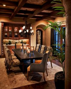 Warm tones, candle chandelier, and dark dining table give this dining room lots of warmth