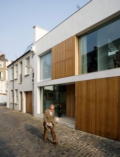 New Mews House | Jonathan Tuckey Design, West London, UK - Lye treated, oak shutters to create a new facade within the existing mews.