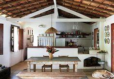 O telhado em duas águas, com tesouras aparentes, cobre a área social e a cozinha com fogão a lenha. Algumas panelas ficam expostas na prateleira da parede, ao fundo. Outras, na estante, escondidas por uma cortina de renda