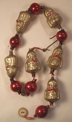 """ANTIQUE Vtg Mercury Glass Feather Tree Garland Santa - strand of antique, mercury glass garland is approximately 18"""" long. The six, sweet little Santas are double sided and about 1.5"""" in length. The six red bulbs are approximately 1"""" long. This great old garland is most likely early 20th century It's strung on red string and secured with an old shell button. The Santas are a silvery color with hand painted, red detail Z"""