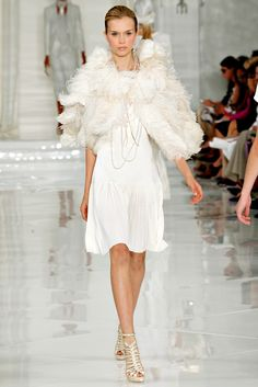 3/1/15 This dress is inspired by the 1920s because of the light colors, straight silhouette, and length of the ensemble. The long pearl necklace was also very popular during the 1920s, as well as the fur/feather boa.