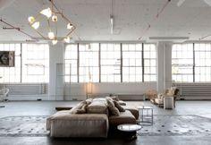 Il divano Extrasoft di Piero Lissoni per Living Divani e, in primo piano, il tavolino di pietra e ferro Millstone di Patrick Weder. I tavolini tondi in acciaio e vetro fanno parte della serie Ile Side Tables di Lissoni per Living Divani