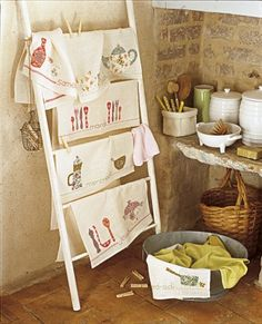 kitchen dishcloths = embellish plain kitchen towels for each day/week + hang in kitchen for easy access. (marieclaireidees.com) maybe use an old garden trellis instead of ladder? and hang on the wall to prevent a messy bump-and-fall...