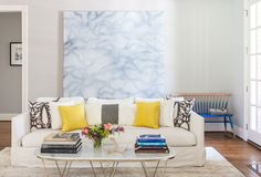 In the living room, a pair of deep Verellen sofas (one is pictured) picked up at Atlanta's South of Market frame Worlds Away's gold-and-marble Surf table. An ombre bench from Anthropologie creates a seating nook besides an acrylic work by Crowell's artist husband, James Wilson.