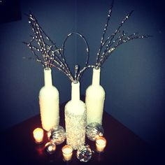 DIY wine bottle Xmas decor! White spray primer- let it dry. Spray adhesive put the pretties on! (I used Epsom salt on the back two and loose silver glitter) cheap, easy, pretty!