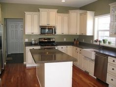 I think this is the sage green wall color I've been looking for.  It goes well with white cabinetry and wood floor tones.  Now imagine with pops of red and copper.  Even the dark counters are on my list!