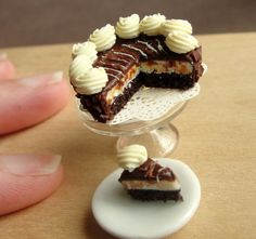 """""""Kim Burke's miniature food sculptures are so realistic you'll want to eat them... Inspired by the photorealist movement, Burke creates flawless dollhouse-scale meals from actual photographs... Each plate of food, so small as to be balanced on a human fingertip, is carefully rendered from clay... Chalk pastels add color. For cake frosting, Burke uses Translucent Liquid Sculpey mixed with solid clay. The artist's company, Fairchild Art, offers a range of plates.. each at a 1:12 scale."""""""