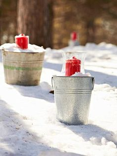 Heavy-duty luminarias, made from snow-filled metal pails and candleholders, outline a path during the day -- and light it at dusk.