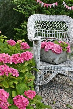 Antique Wicker Chair and basket in a flower garden.