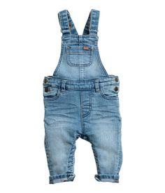 Light denim blue. Bib overalls in soft stretch denim. Adjustable suspenders with snap fasteners, bib pocket, front pockets, and back pockets. Seam at waist