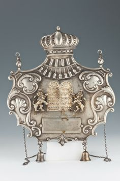 """A SILVER TORAH SHIELD BY POSEN. Frankfurt-Au-Main, c. 1920. In cartouche shape. Decorated with applied lions, the Decalogue and a crown. 10""""..."""
