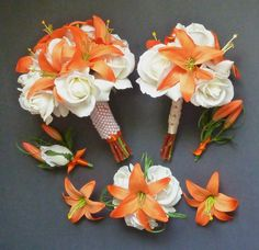 white rose bouquet with orange lilies.. perfect for my bridesmaids expect with navy wrapping