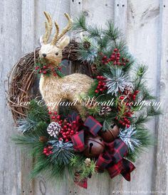 """Woodland Deer Holiday Wreath. Abundant silk mixed pine boughs accented with clusters of rich red berries, pine cones and delicate frosted pine grace the edge of a rustic grapevine frame. An 18"""" sisal"""