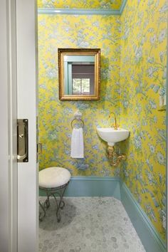 A pocket door, a miniature corner sink with decorative plumbing, and arresting floral wallpaper trimmed with aqua-painted baseboards make the most of the 3-by-6-foot first-floor half bath.