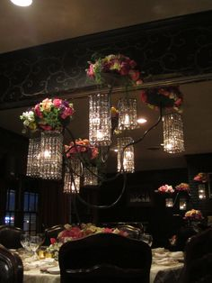 Elegant display of spring flowers colors including pinks, purples, yellows, greens and purples. Flower types including hydrangea, stock, roses, spray roses, garden roses, and mini callas. Flowers are displayed with hanging crystal lights on stand custom made by Holliday Flowers.